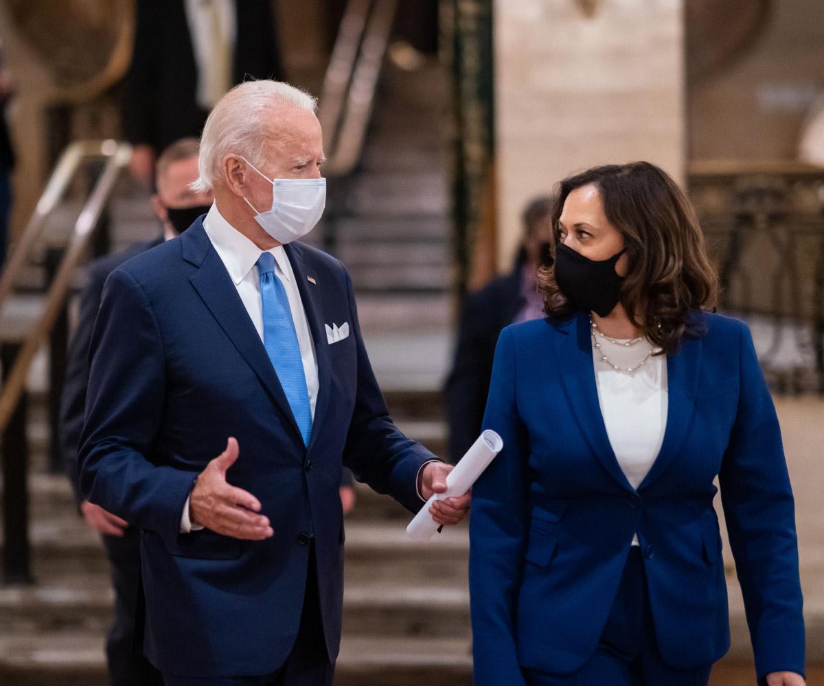 El presidente Biden y la vicepresidente Harris hablan entre ellos mientras usan máscaras y trajes azules