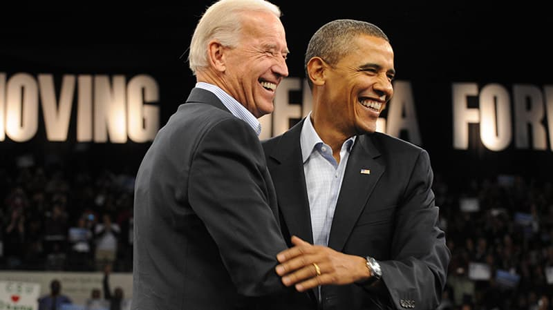 Joe Biden and Barack Obama both in dark suits, holding each other and smiling