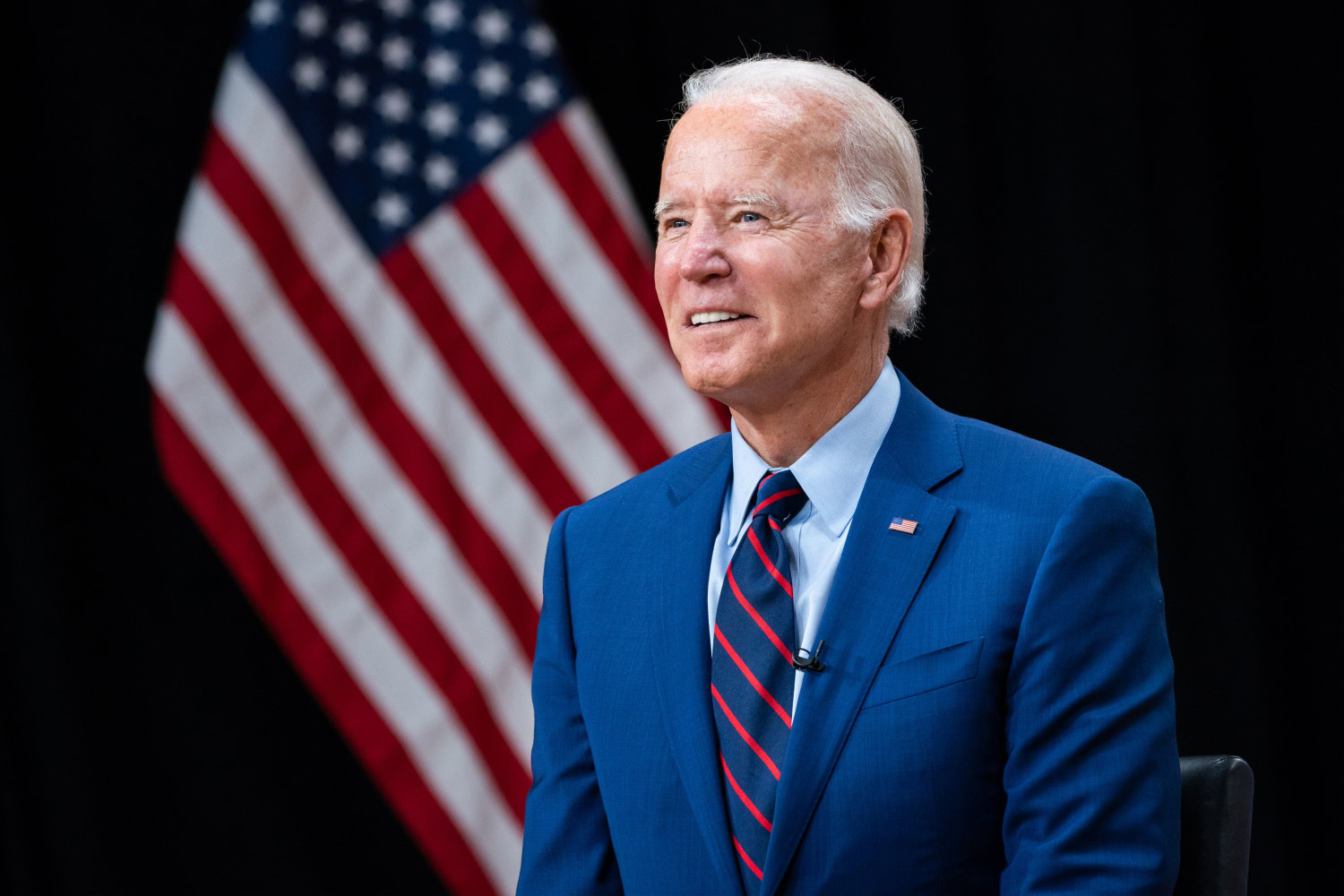 President Joe Biden wearing a suit, standing in front of an American flag