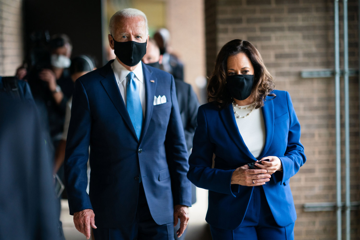 President Biden and Vice President Harris walking while wearing masks.