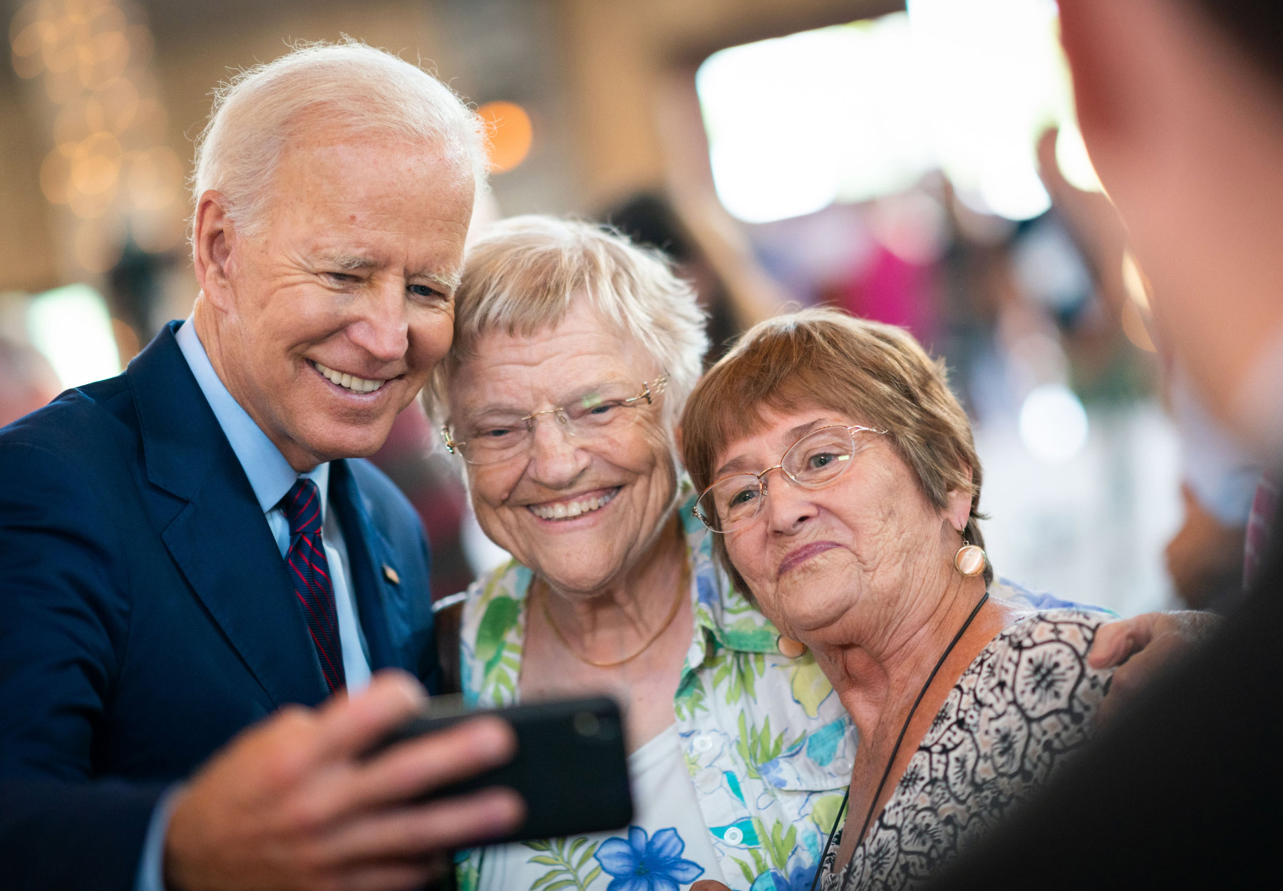 President Joe Biden takes a photo with attendees at an event in Burlington, IA