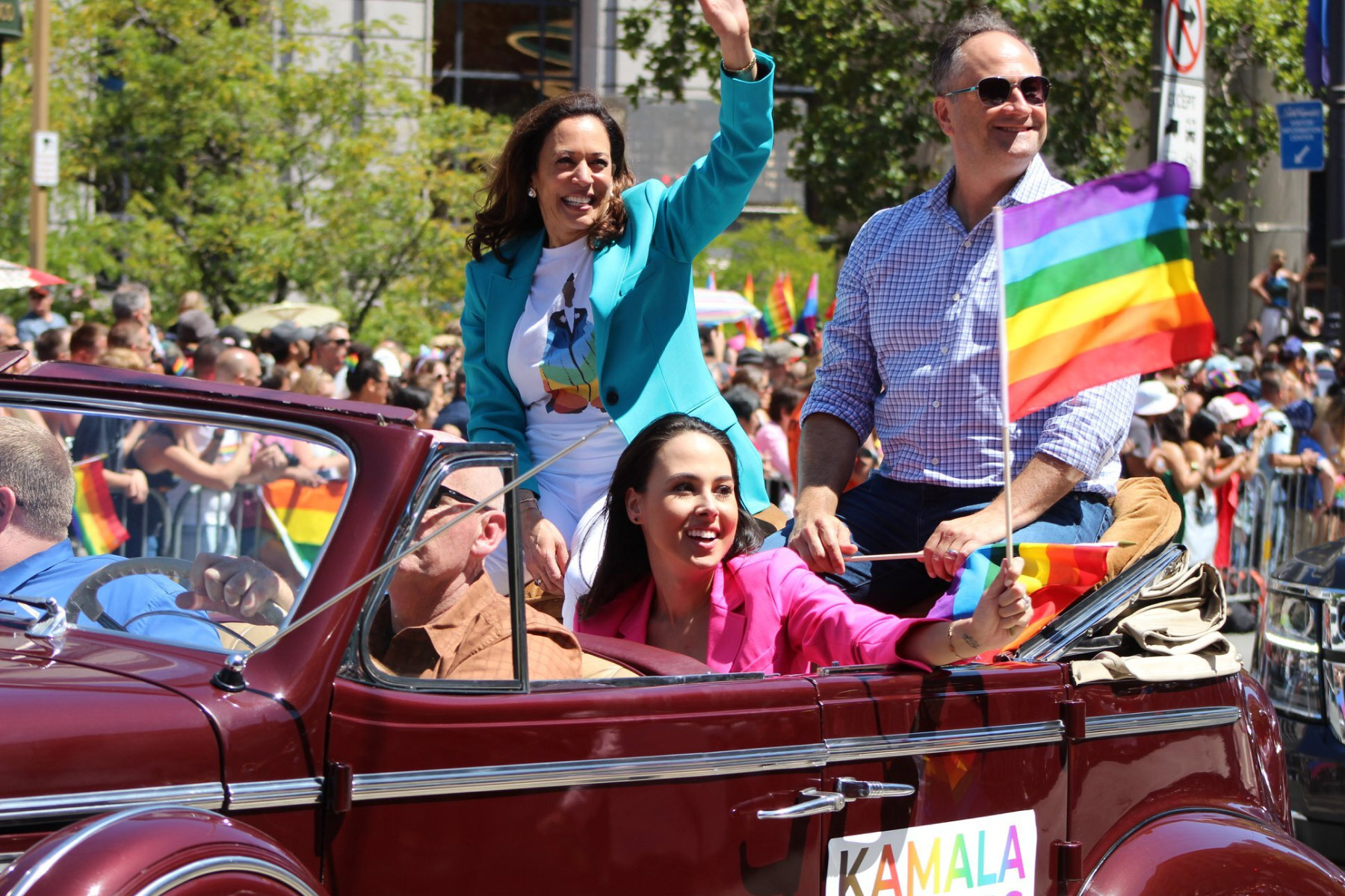 Vice President Harris smiles at a crowd at the Pride Parade in San Francisco, CA, accompanied with her husband, Doug, and her niece, Meena